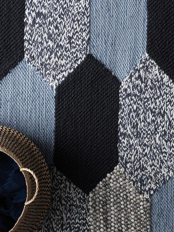 Una alfombra con un diseño que entremezcla formas y colores, y sobre la que hay una cesta.