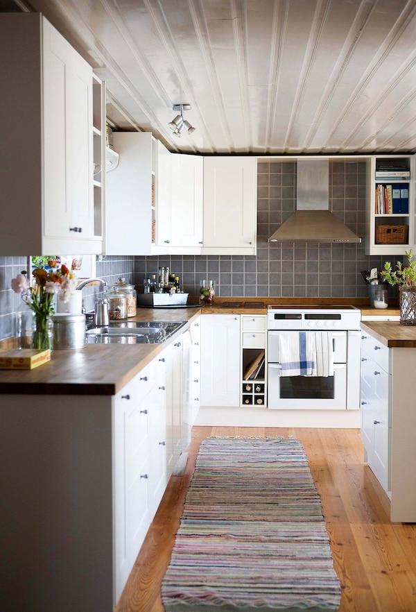 Una alfombra larga y estrecha de rayas ayuda a crear un estilo rústico en esta cocina grande y blanca.