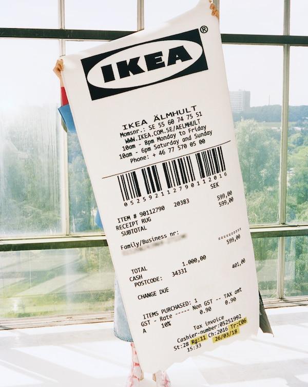 Una alfombra MARKERAD con la forma de un recibo gigante de IKEA se sujeta ante la cámara.