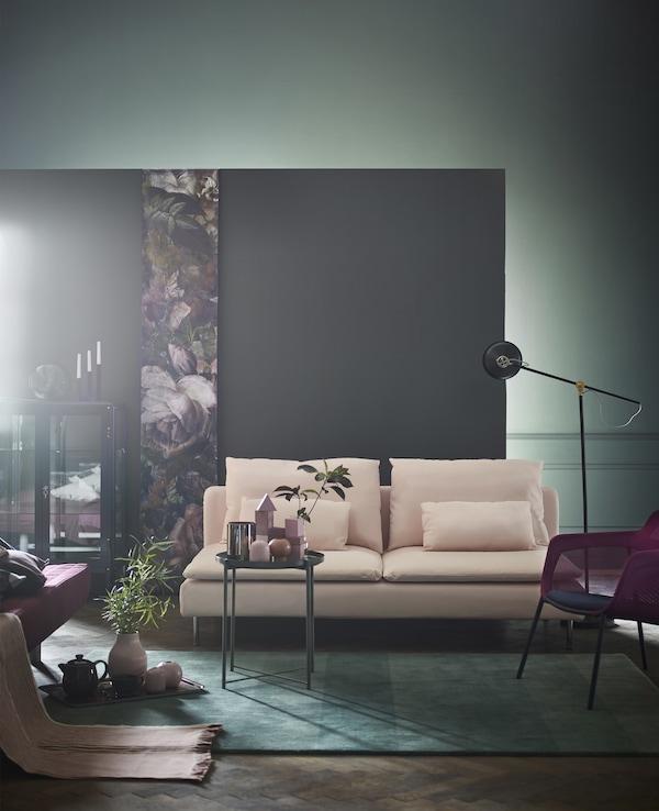 Una alfombra verde, una mesa con bandeja verde y un sofá modular de tres plazas SÖDERHAMN de color rosa claro en un salón con una pared gris.
