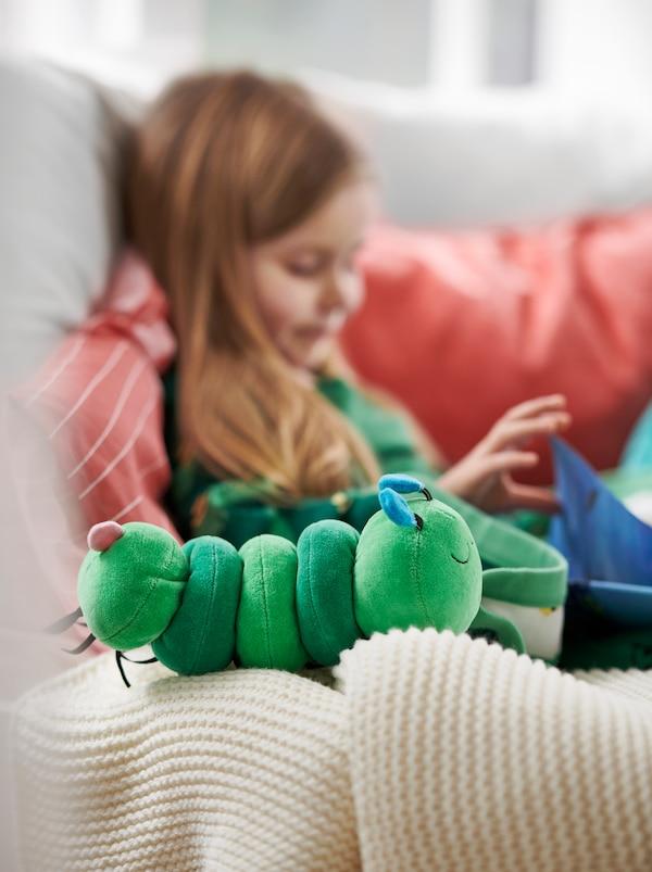 Una bambina, seduta su un divano con cuscini rossi, che legge un libro vicino a un giocattolo musicale, il bruco di peluche KLAPPA.