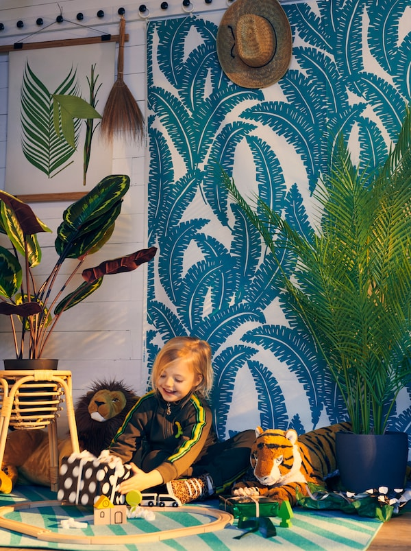 Una bambina tiene in mano un regalo incartato in una stanza con delle piante, tessuto a metraggio UGGLEMOTT alle pareti e un tappeto GRACIÖS che creano un'atmosfera da giungla - IKEA