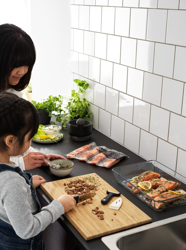 Una bambina usa un coltello SMÅBIT per affettare mandorle sul piano di lavoro nero di una cucina, aiutando la mamma a preparare una ricetta con il salmone.