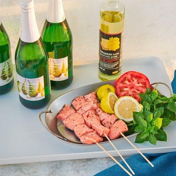 Una bandeja con ruedas con un filete de salmón SJÖRAPPORT listo para la barbacoa y botellas con bebida de pera con gas no alcohólicas.