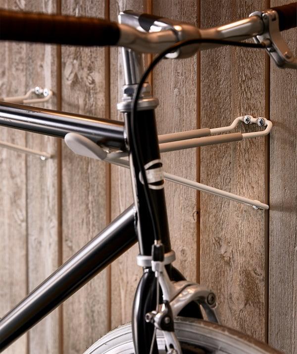Una bici appoggiata a due ganci perpendicolari alla parete - IKEA-up of how the bike frame rests on the rack, consisting of two slim hooks perpendicular to the wall.