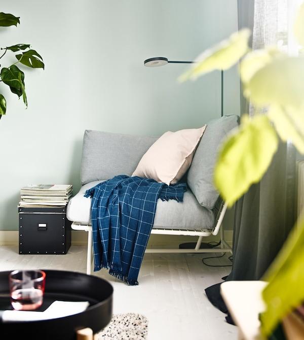 Una butaca cantonera IKEA PS 2017 amb coixins i una manta blava.