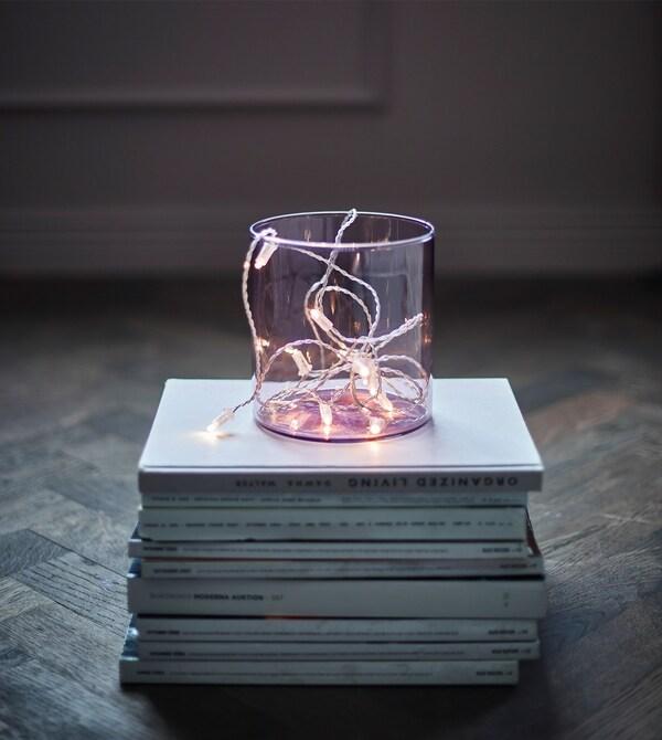 Una cadena de luces LED en un jarrón claro sobre una pila de revistas.