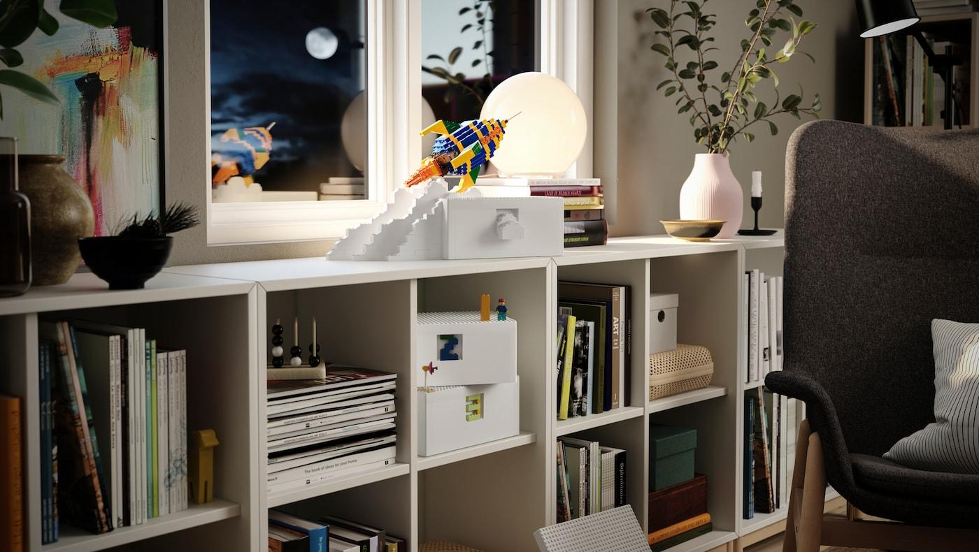 Una caja blanca BYGGLEK sobre un sistema de almacenaje KALLAX; al lado hay un cohete fabricado con bloques LEGO.