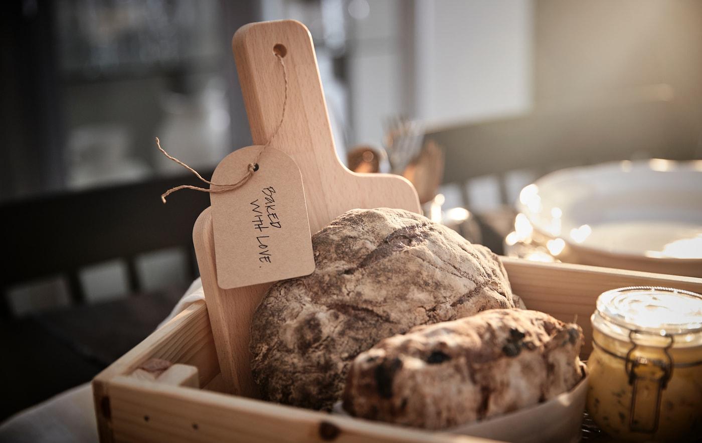 Una caja de madera llena de hogazas de pan, una tabla de cortar con una etiqueta de regalo y un tarro de cristal.