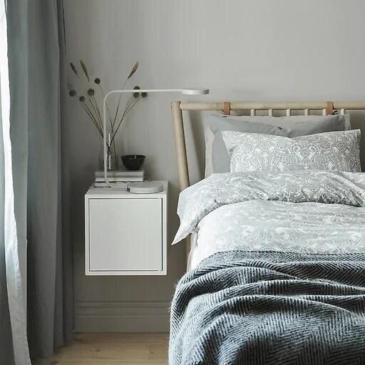 Una cama con capas de ropa en gris con estampados y una mesilla de noche blanca.