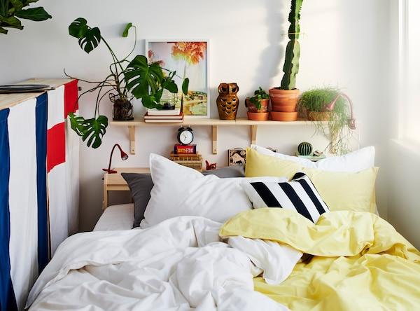 Una cama entre una ventana y la parte trasera de un módulo de almacenaje, con muchas almohadas y ropa de cama en amarillo, blanco, negro y gris.