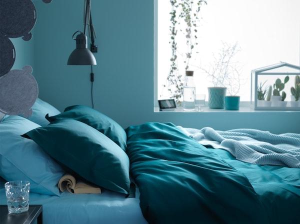 Una cama situada junto a la ventana y llena de textiles en verde y azul oscuro en una habitación azul.
