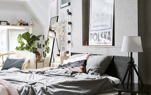 Una camera da letto con biancheria grigia, pareti bianche e una poltrona in rattan – IKEA