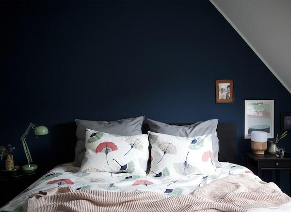Una camera da letto con pareti blu scuro e copriletto coordinato – IKEA