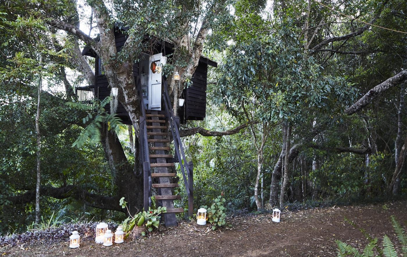Una casa en un árbol en el jardín de Margaret con farolillos blancos en la parte inferior de la escalera.