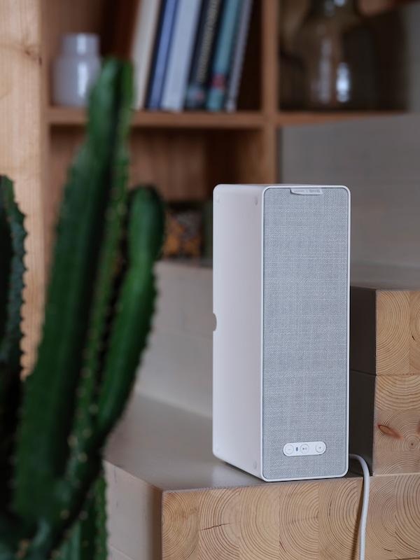 Una cassa Wi-Fi da scaffale SYMFONISK bianca appoggiata su delle scale in legno davanti a una libreria - IKEA