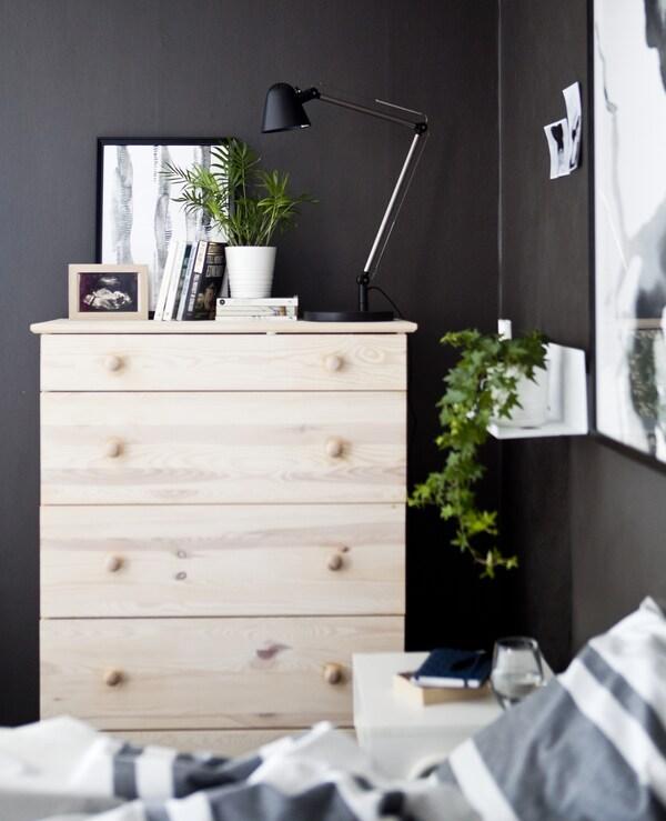 Una cassettiera di legno chiaro in una camera da letto grigio scuro – IKEA