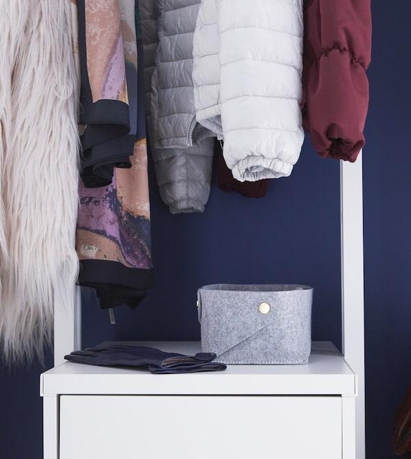 Una cesta de fieltro PUDDA gris sobre un armario debajo de chaquetas colgadas en un raíl para ropa en el recibidor.