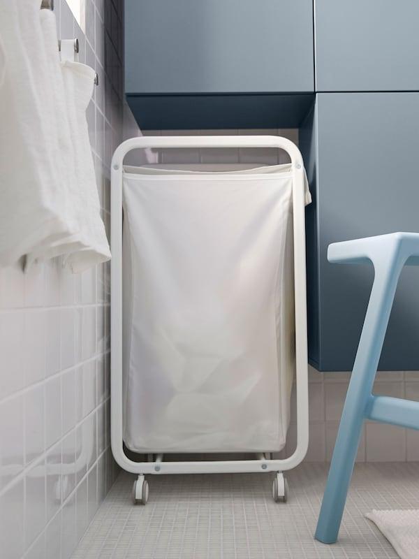 Una cesta de lavandería blanca en el espacio entre el armario y la pared en un baño pequeño.
