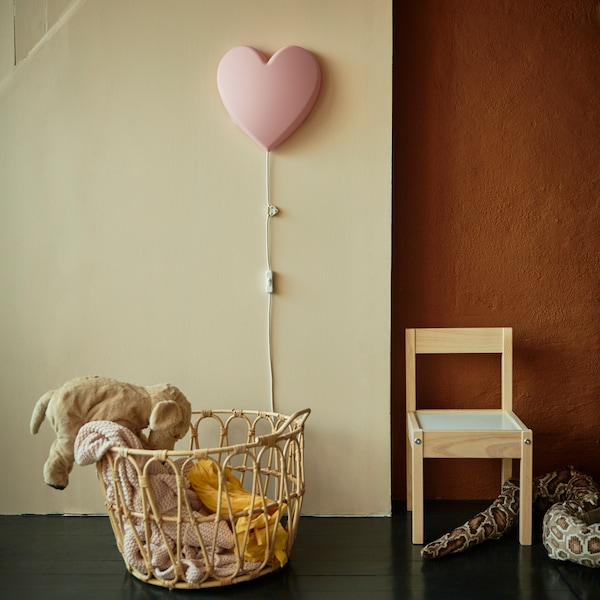 Una cesta de mimbre con un peluche, una silla de niños y un aplique en forma de corazón en la pared para iluminar la zona de juego, de IKEA.