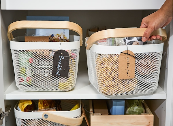 Una cesta de rejilla de acero IKEA RISATORP blanca para organizar alimentos por tipos o alérgenos.