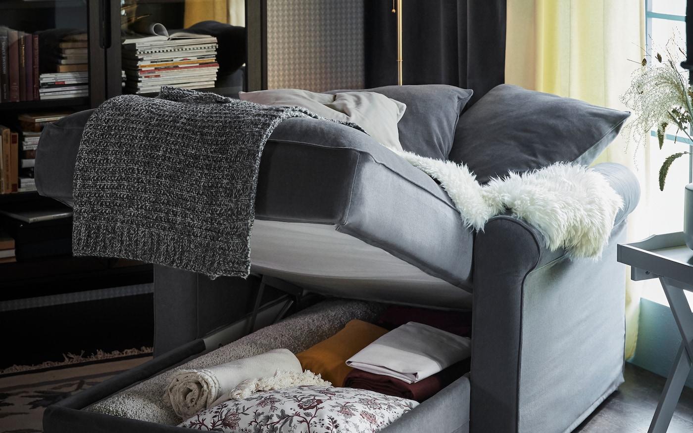 Una chaiselongue GRÖNLID gris con almacenaje integrado debajo del asiento, abierto para mostrar mantas y cojines extra.