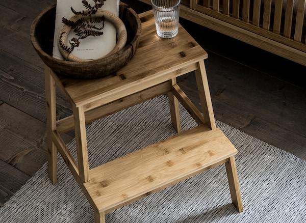 Una ciotola in legno e un bicchiere d'acqua appoggiati su una scaletta/sgabello TENHULT di IKEA realizzata in bambù.