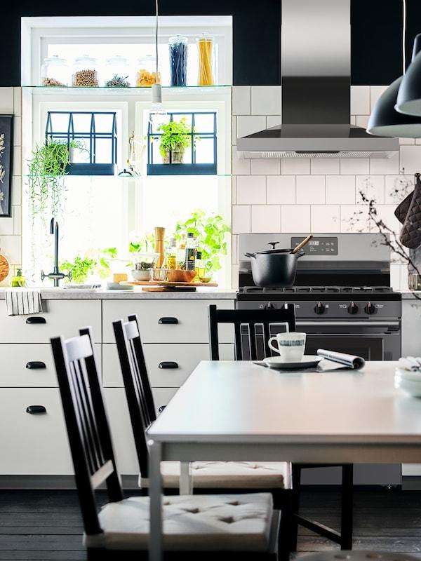 Una cocina con frentes de cocina VEDDINGE blancos y tiradores negros. Hay una ventana grande de estilo tradicional con hierbas.