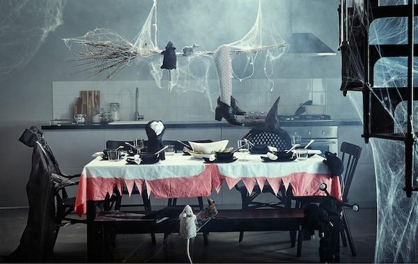 Una cocina con una mesa grande decorada para Halloween.