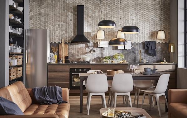 Una cocina, salón, comedor de plano abierto con sofás de piel marrón y armarios de cocina de madera oscura delante de una pared alicatada.