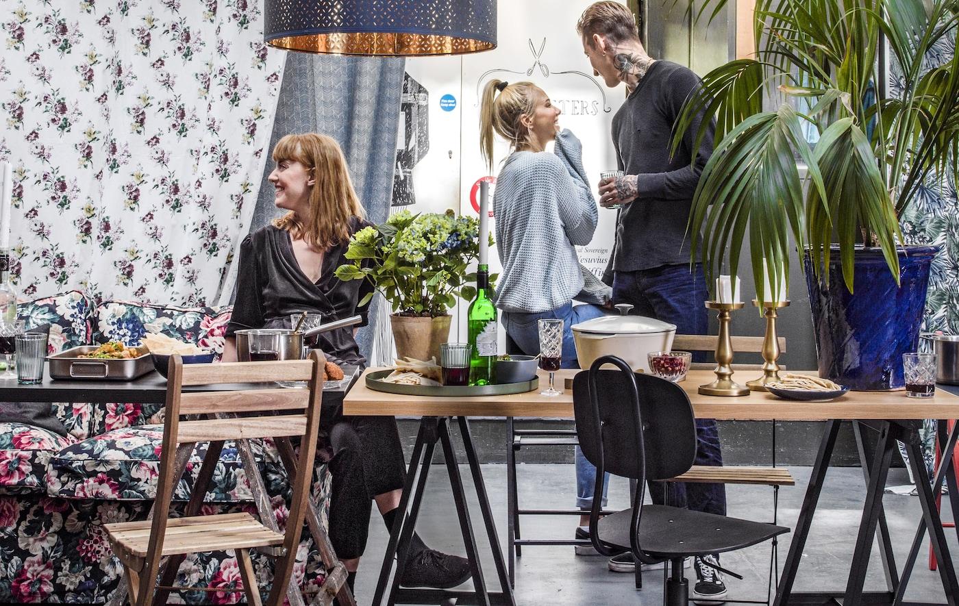 Una col·lecció de taula de menjador i cadires amb unes quantes persones conversant.