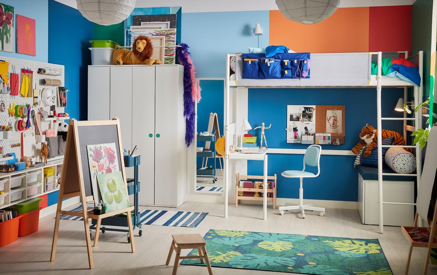 Una colorida sala para niños con una cama alta blanca, un caballete, una alfombra con dibujos de hojas y una silla de escritorio azul para niños.