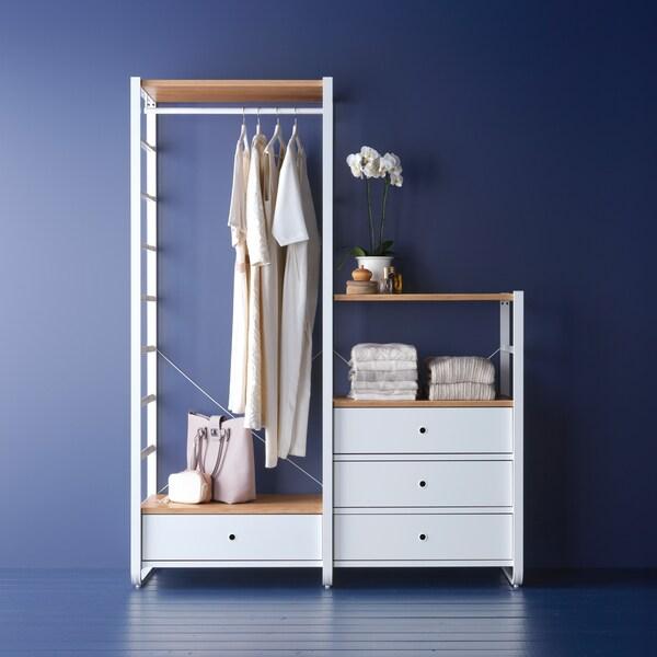 Una combinación de armarios ELVARLI en una habitación azul, con ropa en una barra, bolsos y otros objetos.