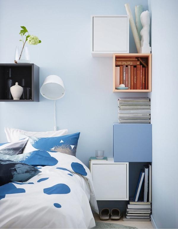 Una combinación de mesilla de noche hecha con coloridos armarios de formas cúbicas colgados en las paredes alrededor de la cama.