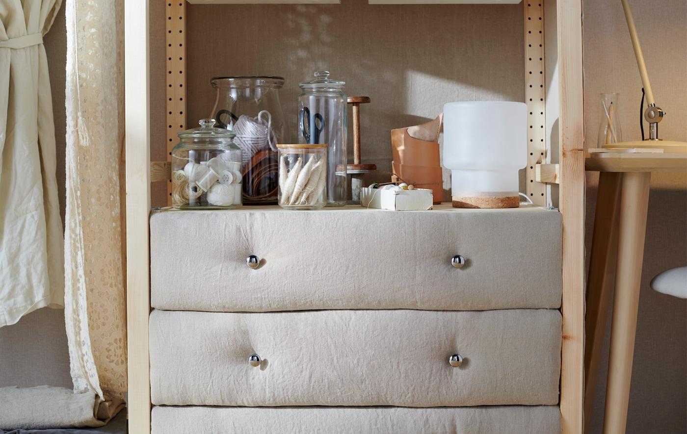Una cómoda IKEA IVAR de tres cajones forrados con tejido en la parte frontal. Útiles de costura metidos en tarros decoran la parte superior.