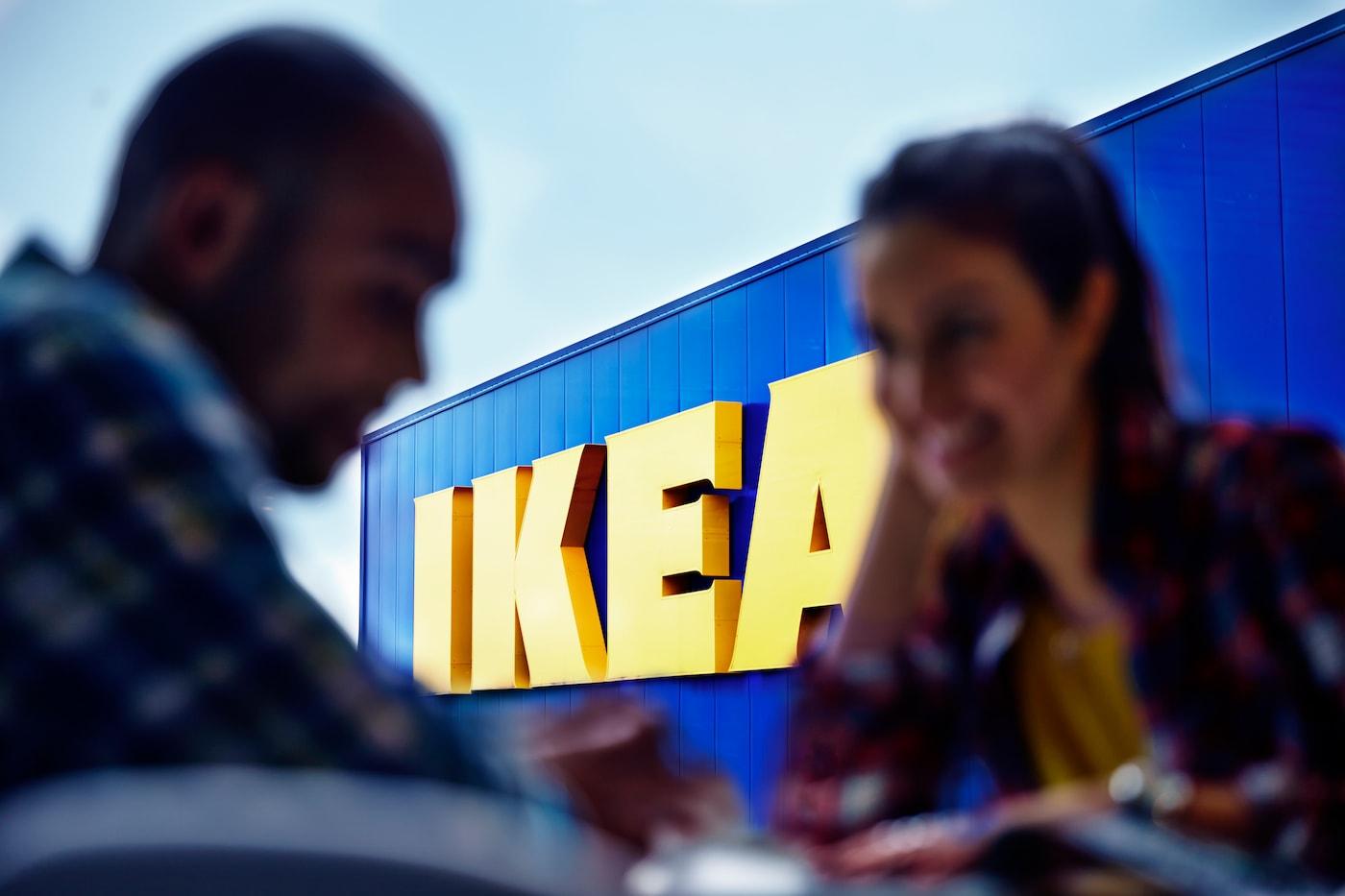 Una conversación entre un hombre y una mujer, donde ambos sonríen y tienen de fondo una tienda IKEA con el logo grande con los colores azul y amarillo.