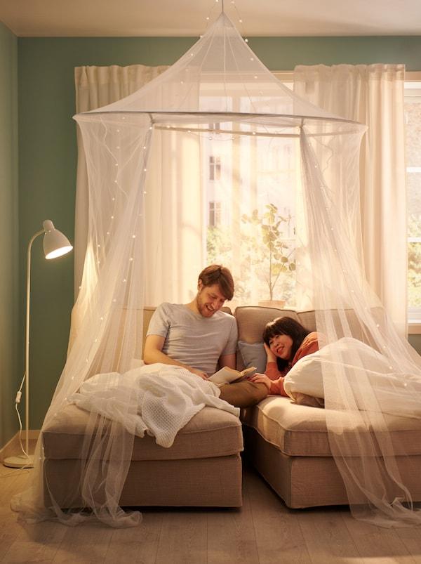 Una coppia sdraiata su due chaise-longue davanti a una finestra illuminata dal sole, dei copriletti VÅRELD e una rete SOLIG drappeggiata attorno - IKEA