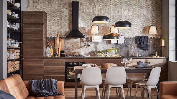 Una cucina con mobili in legno marrone scuro effetto noce, tre lampade a sospensione nere, un tavolo marrone scuro e sei sedie.