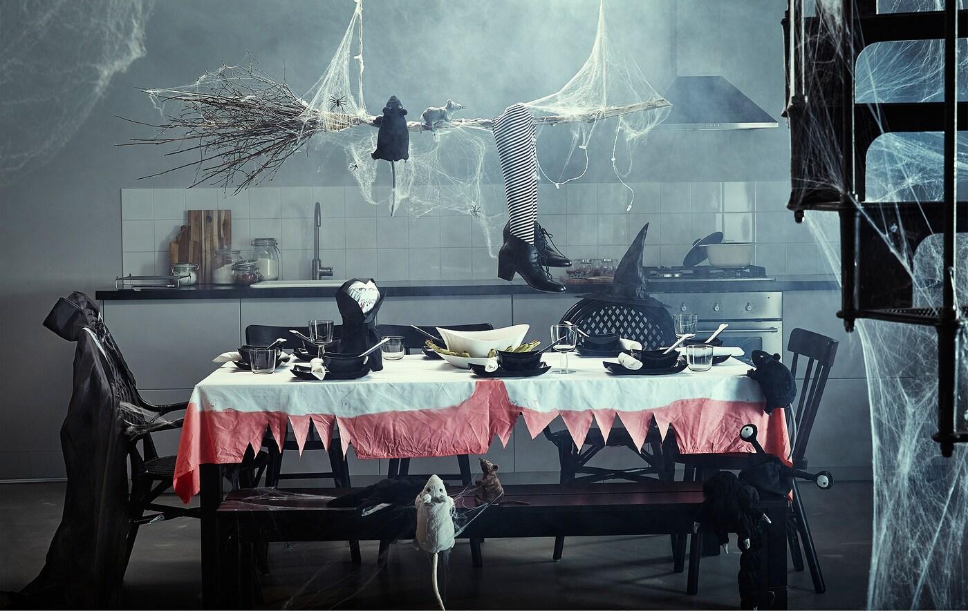 Una cucina con un grande tavolo pieno di decorazioni per Halloween.