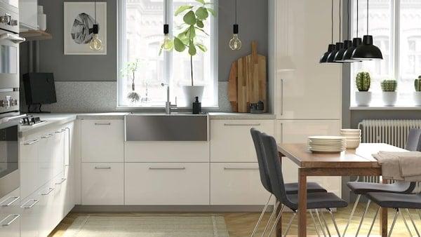 Una cucina IKEA METOD moderna e luminosa, con ante e cassetti RINGHULT bianchi, con lavello in acciaio inox, in uno spazio abitativo aperto.