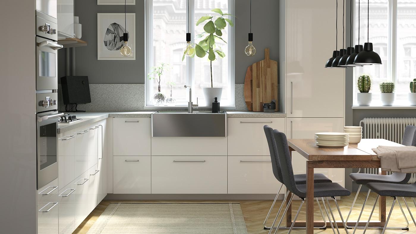 Una cucina luminosa con frontali dei cassetti bianchi e lucidi, pareti grigie, un tavolo in legno e un lavello in acciaio inossidabile.