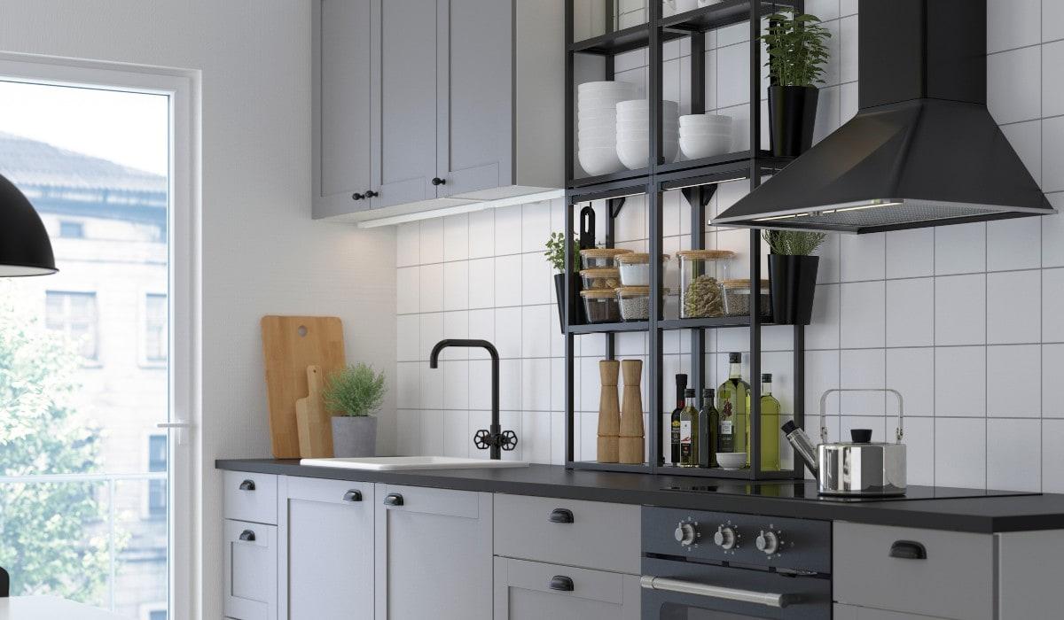 Una cucina luminosa con mobili e cassetti grigi, pareti piastrellate bianche e scaffali aperti neri.