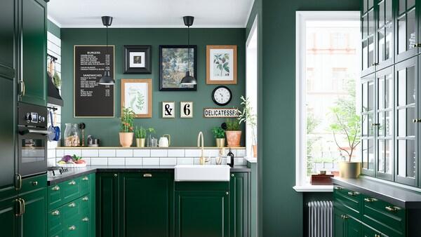 Una cucina verde con un lavello bianco con frontale a vista, un miscelatore color ottone, un piano cottura a gas e due lampade a soffitto nere.