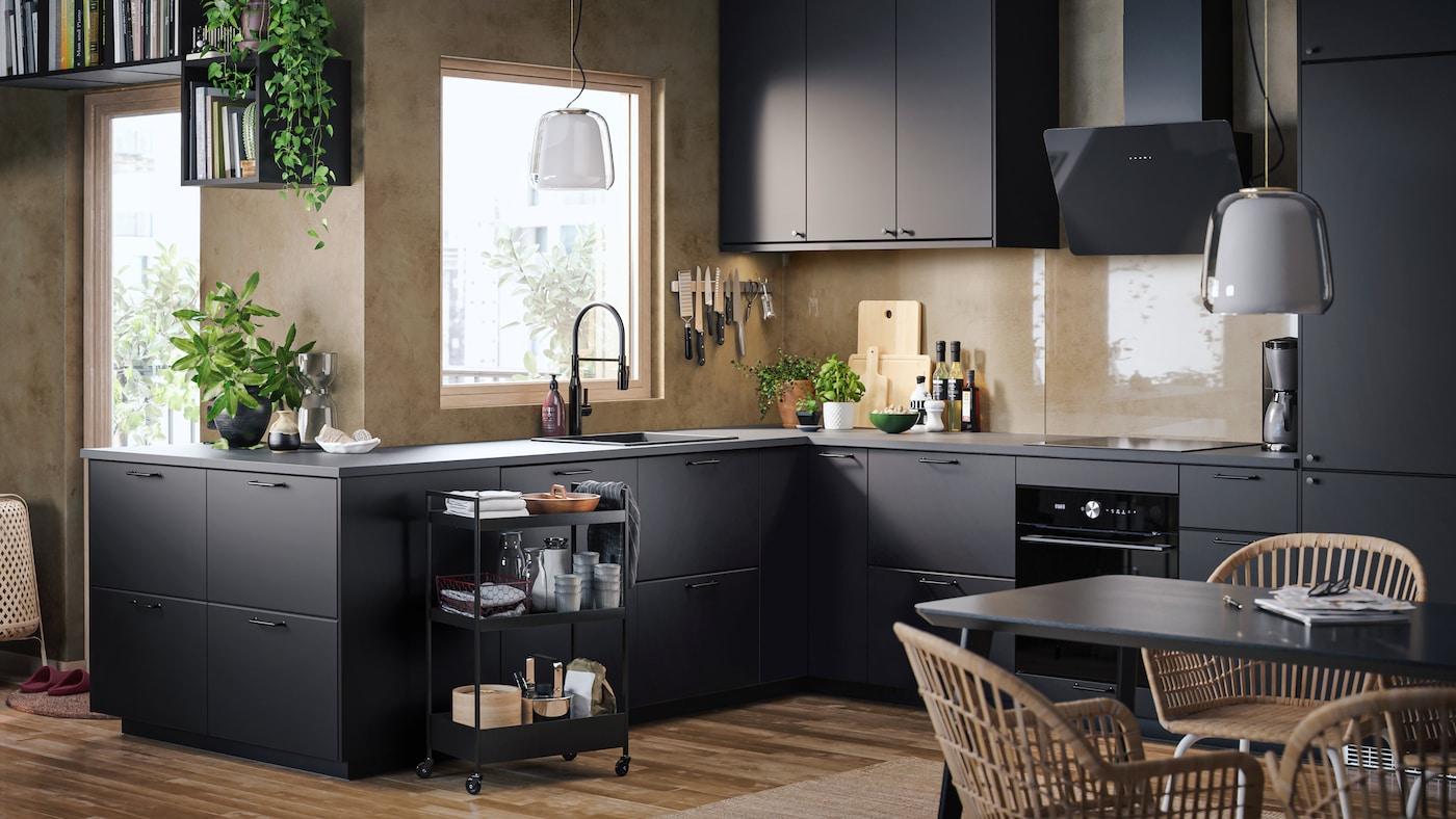 Una cuina amb parets de color beix, parquet, frontals de cuina KUNGSBACKA de color antracita i un carretó amb estris de cuina.