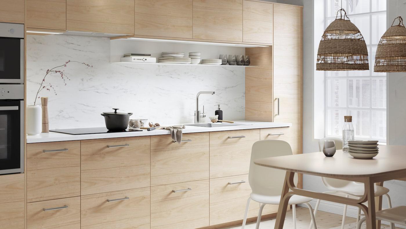 Una cuina ASKERSUND d'efecte freixe clar amb un taulell EKBACKEN d'efecte marbre blanc. Hi ha una cassola damunt la placa d'inducció.