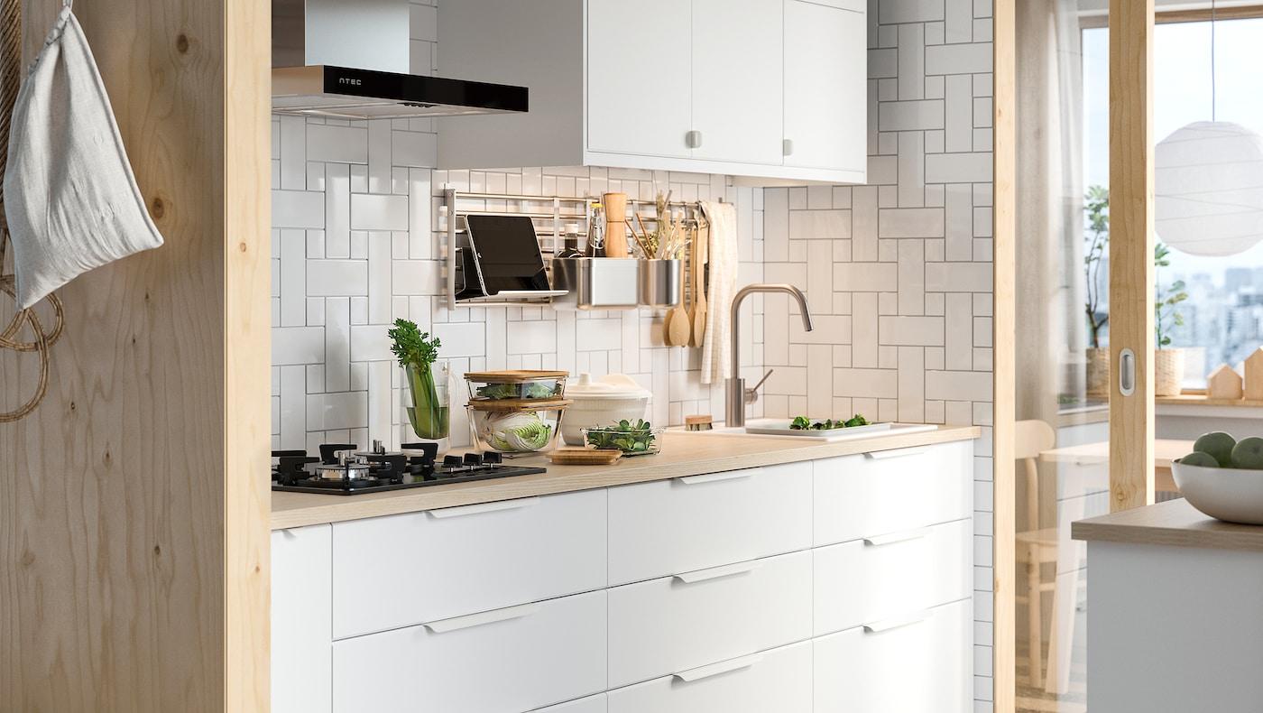 Una cuina blanca amb calaixos blancs KUNGSBACKA sota d'un taulell de fusta pàl·lida i un armari de paret blanc a sobre.