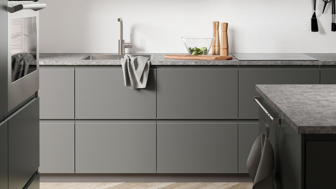 Una cuina de color gris fosc amb frontals de cuina de color gris fosc VOXTORP, un taulell amb efecte pedra de color gris fosc i una illa.