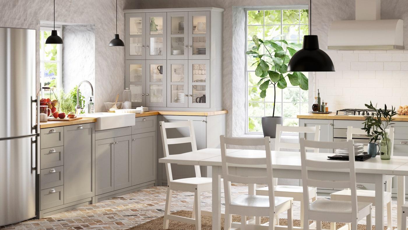 Una cuina lluminosa d'estil tradicional amb frontals de cuina LERHYTTAN de color gris clar, una taula NORDVIKEN i cinc cadires blanques.