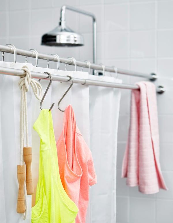Una de las dos barras de cortina de la ducha se usa para colgar toallas y la ropa del gimnasio.