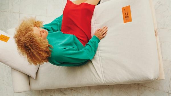Una dona es reclina còmodament sobre un sofà llit de fusta amb matalàs gris.